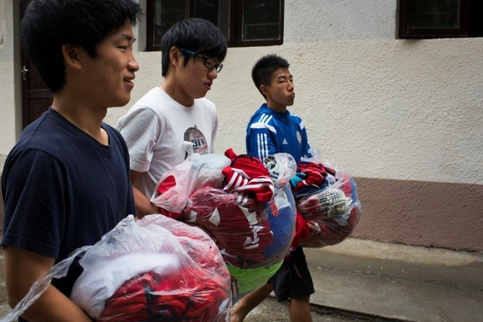 Lee Seon Cheoi, (left to right) Kaito Akimoto, and Chison Ko carry laundry for their team, United Koreans in Japan, to a laundry facility at their hotel on June 2, 2016 in Sukhumi, Abkhazia. Koreans living in Japan constitute one of the largest groups of ethnic minorities in the country. (Pete Kiehart for ESPN)