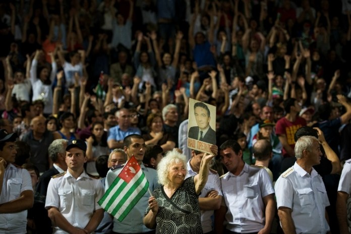 Lyuba, 79, holds an Abkhazian flag and a portrait of the first president of Abkhazia, Vladislav Ardzinba, after Abkhazia's victory over Panjab in the CONIFA Final on June 5, 2016 in Sukhumi, Abkhazia. (Pete Kiehart for ESPN)