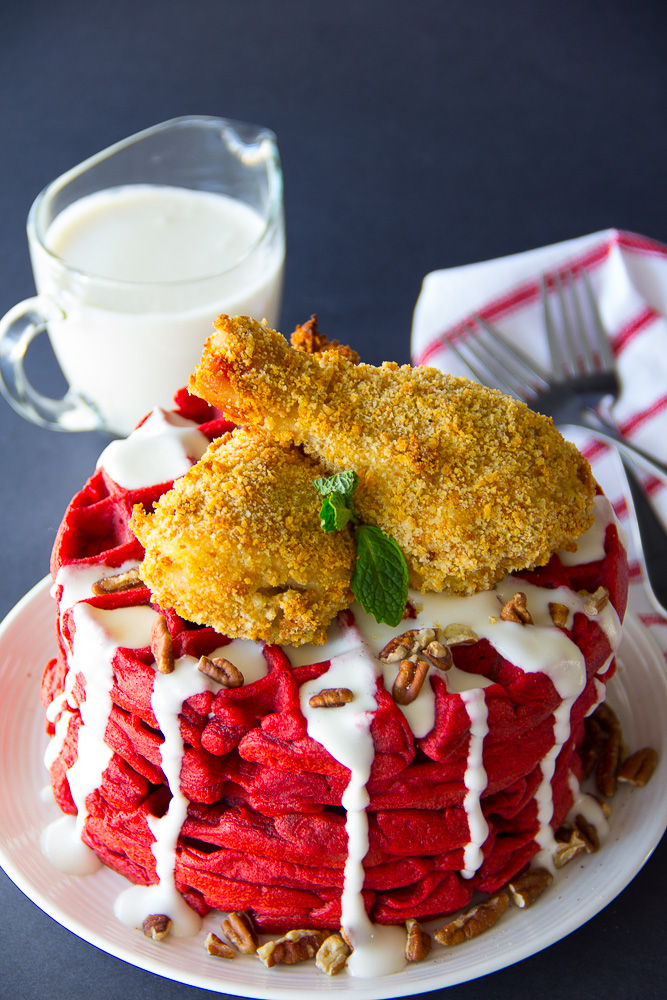Unbelievably spectacular red velvet waffles bathed in a delicious cream cheese icing get topped with guiltless yet crispy oven fried chicken!