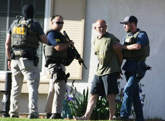 Adelanto Mayor Rich Kerr stands in handcuffs as FBI agents execute a federal search warrant at his home Tuesday morning. Photo by: James Quigg, Daily Press