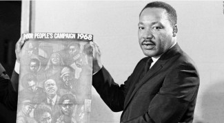 Dr. Martin Luther King displays the poster to be used during his Poor People's Campaign, March 4, 1968, one month before he was shot to death by a sniper.