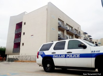 A Dallas Police vehicle is parked near the South Side Flats apartments, Sept. 10 2018, in Dallas.