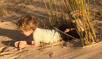 Laying on the sand and letting it just run through his hands