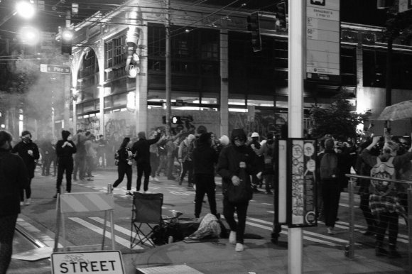 Broadway and Pine, Capitol Hill, Seattle, almost midnight, 1 July 2020. The crowd briefly scattered after what I assumed was a police flash bang. In this instance, it was a protestor who first set something off. I saw the sparkling fuse and assumed it was a firecracker that prompted a flash bang response, but I now think it might have all been the protester. People were not happy. One woman was yelling that whoever did that needed to leave. My first thought was that whoever did that is going to get someone killed.