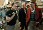 """David Milch, left, creator of the HBO series """"Deadwood,"""" demonstrates how actor Larry Cedar, center, should pull a cart on Deadwood's main street as actor Peter Jason watches during filming Wednesday, Feb. 9, 2005, in Santa Clarita, Calif. (AP Photo/Kevork Djansezian)"""