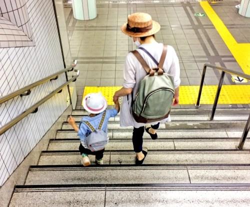 手をつないで階段を下りる親子