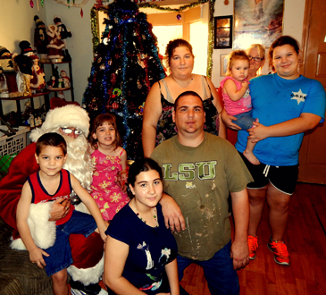 Shown with Santa, portrayed by Col. David Mowers, is the family of Angelina Lema, standing in the back row.