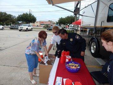 Karen Salathe of Chalmette puts prescription drugs in a take-back container, assisted by Capt. Pat Childress and Maj. Chad Clark of the Sheriff's Office.