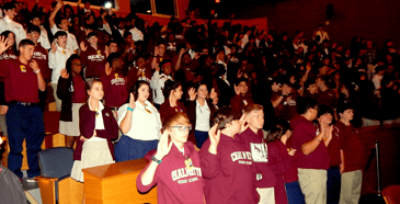 Students stand with an arm raised to take the gun violence pledge.