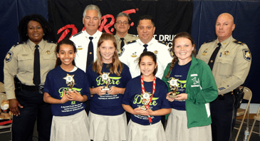 D.A.R.E. essay winners at Davies Elementary were, from left, Penelope Pagoaga, Madisyn Clark, Sophia Vitrano and Felicity White. In the back row are D.A.R.E. program supervisor Lt. Lisa Jackson, Sheriff James Pohlmann, D.A.R.E. instructor Sgt. Darrin Miller, Maj. Chad Clark and Capt. Ronnie Martin.
