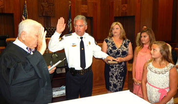 Sheriff ames Pohlmann is sworn-in by udge Robert Klees, with the sheriff's wife, Monique, and their daughters Victoria and Olivia at his side.