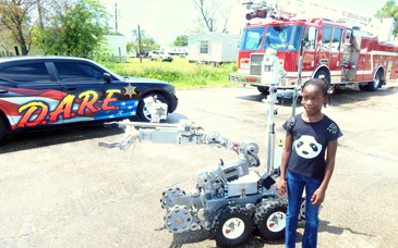 Jashayla Parker, 9, with the Sheriff's Office bomb robot used to check suspicious items, displayed at the One Voice Task Force event.