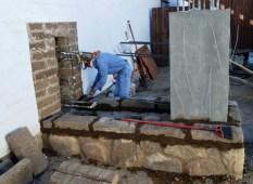 Tim Aguilar laying first course of adobe blocks on sandstone foundation. Photo by Mike Imwalle.