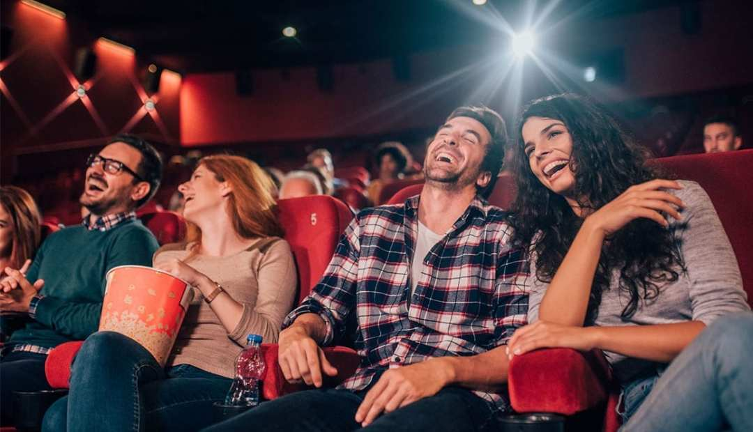 Two Couples laughing in a movie theatre