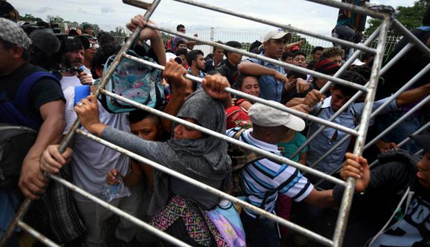 Migrantes hondureños presionan y logran derribar las vallas sobre el puente el puente que cruza el río Suchiate. Foto: AFP