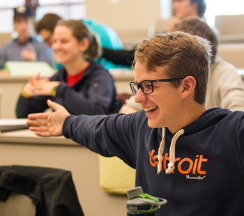 Student smiling and holding arms out to his sides.