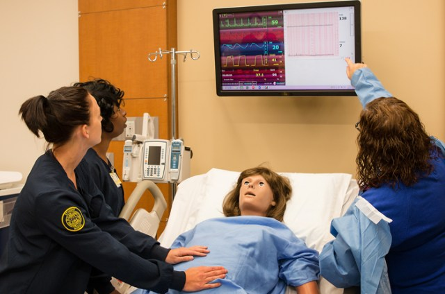 Nursing students with simulation manikin.