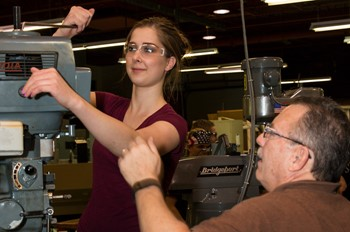 Student working on a machine with assistance from her instructor.