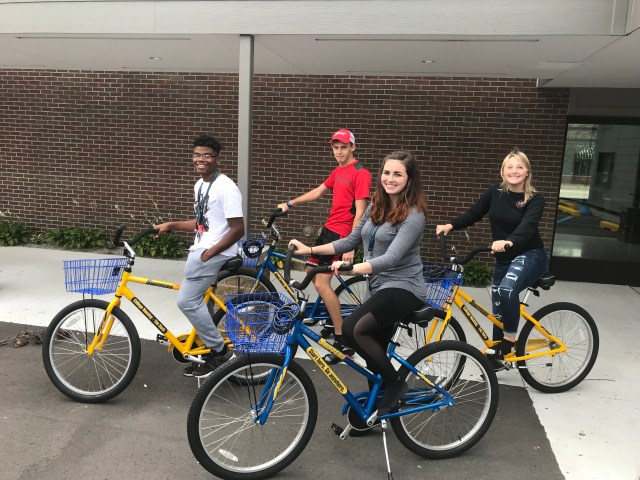 Four housing students ride SC4 bicycles.