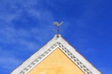 Coq chantant sur le toit d'une maison
