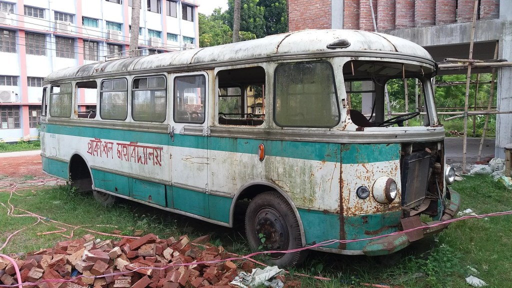 A very beaten up old bus sitting with all the windows smashed, outside some industrial buildings. Everything looks abandoned. There is a green cold tone to the image