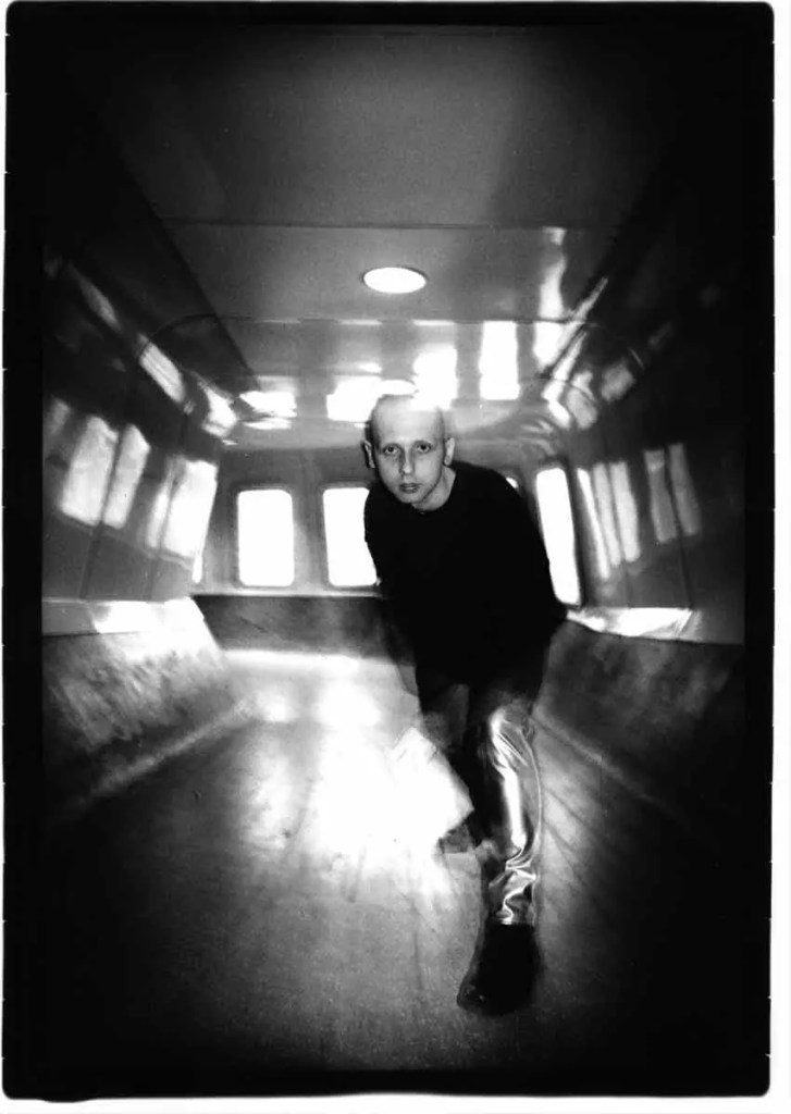 dramatic black and white image of a man in a tunnel, captured with the light moving all around him. He's wearing tight silver trousers and a black knitted jumper. His head is shaved.