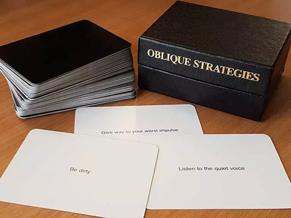A black box of playing cards on a table. There's a pile of cards beside the box and three on display with white background and texts that suggest 'be dirty - give way to your worse impulse' and listen to the quiet voice