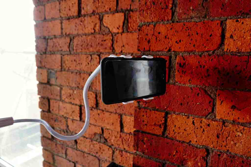 An Apple iPhone is held up in the air by a white stand, pictured against a red brick wall