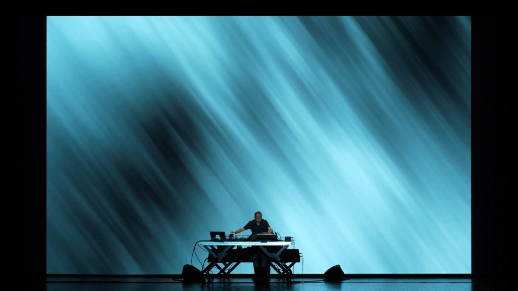 man on stage performing behind a large table, up to his waist. The man is dressed in a smart black shirt but dwarfed completely by a gigantic projection on the wall behind him in blue, with abstract lines across it