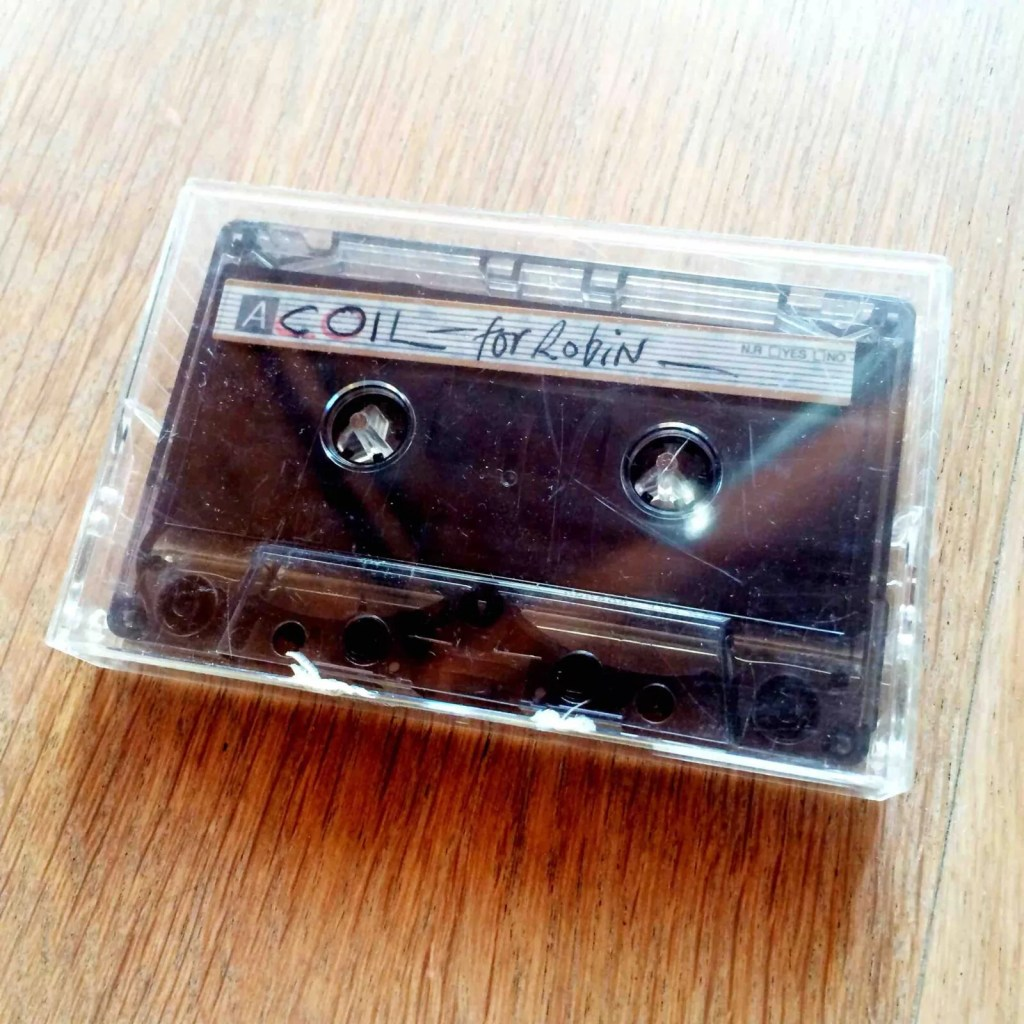A casette tape in a plastic transparent tape box, with a handwritten sticker on the tape 'Coil - for Robin'