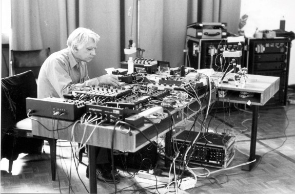 Black and white photograph of an older white man, with white hand wearing a white shirt seated in front of a large table. The table top is completely filled with strange anonymous boxes with wires and cables everywhere