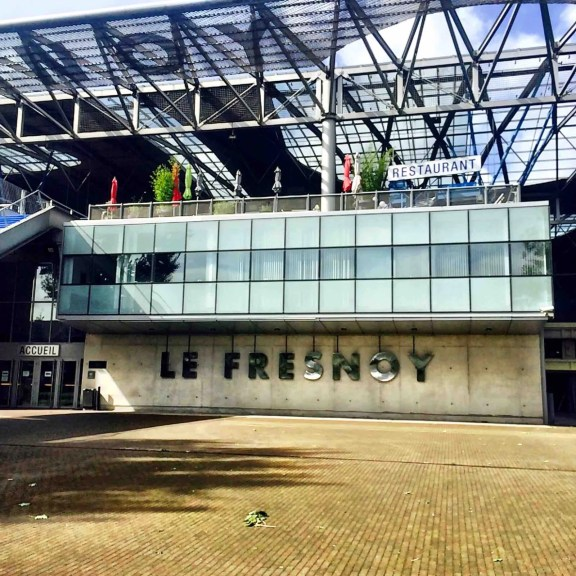 An industrial looking building with bold letters across it - LE FRESNOY, with huge open plan architecture. No people visible