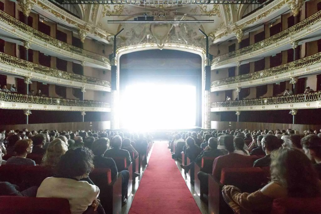 Image from inside a theatre with incredible bright light on the stage, so much that you can only see the light, not the performers. The theatre is filled with people seated looking at the light