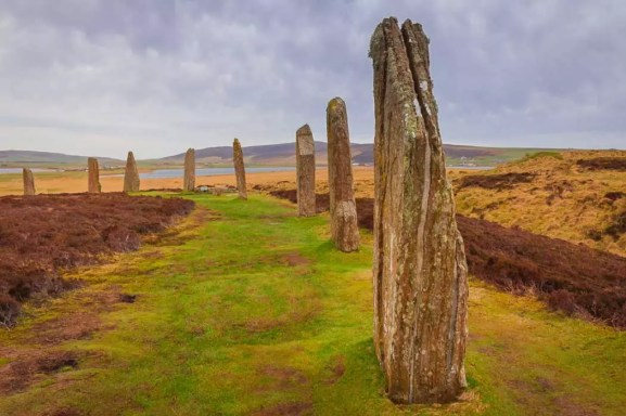 You see a series of ancient stones set up in a line across a photo of a remote landscape in colour