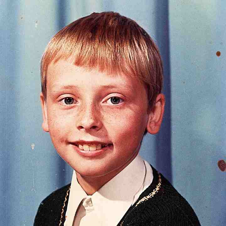 A young boy with blonde hair, aged 11 years old, smiles at the camera, wearing a smart shirt and jumper, with a blue background behind him