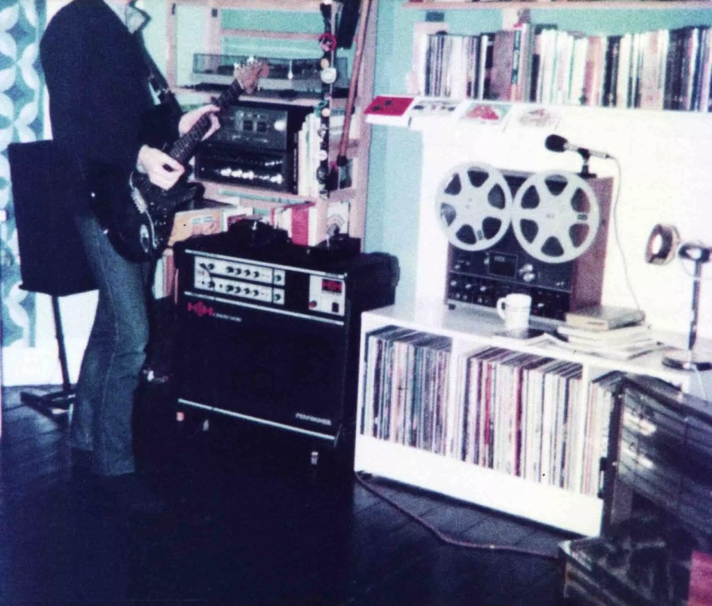 A headless teenage boy plays a black Fender Stratocaster guitar. he wears tight blue jeans and a blue jumper. He stands in his bedroom before an H/H guitar amp, a reel red recorder, and lots of records and books on shelves. His head has been cut off the top of the image.