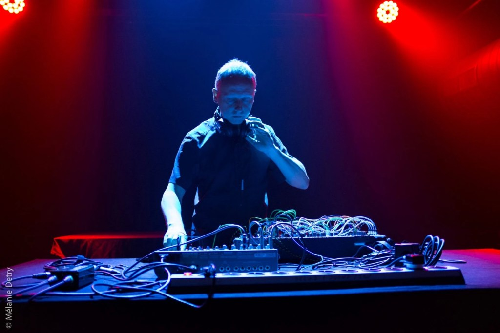 Man stands in front of table of electronic equipment. He is dressed in a smart black shirt and holding his hand to his neck where he is holding a set of headphones. The image is taken on stage at a live concert.