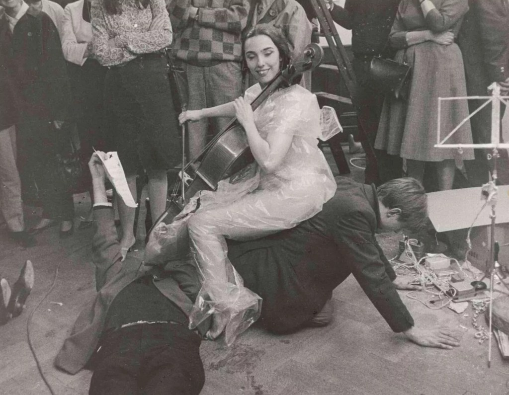 Black and white photo. A woman is naked, covered only by a transparent plastic raincoat. She is playing the cello, with a big smile on her face, sitting on top of a man on the ground on all fours, wearing a suit. There is a crowd of people standing around watching them