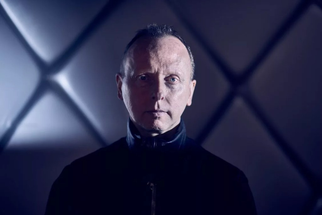 Image of man, aged around 50, serious, staring directly at the camera. Wearing a high neck leather top he has short hair and an intense stare. Behind is an abstract padded wall looking like a cross