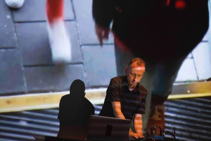 Photograph of a short haired man, Robin Rimbaud, standing at a table, wearing a black shirt, leaning over a computer, in a live musical performance, with a huge projection screen behind him, in a very dramatic pose