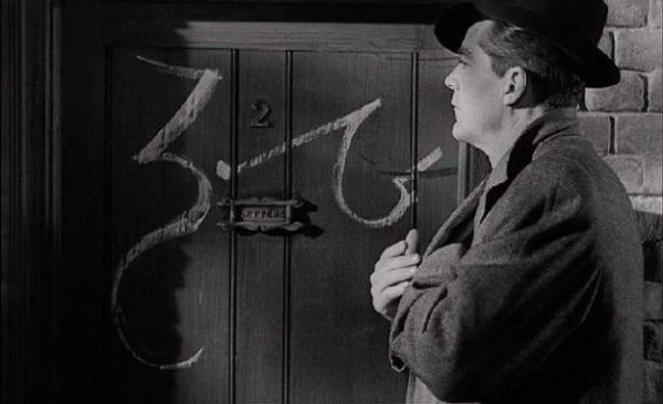 Dana Andrews muses over the strange script on the door in Curse of the Demon (1956)