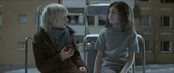 Lina Leandersson (Eli) sizes up Kåre Hedebrant (Oskar) and his Rubik's Cube in Let the Right One In (2008)