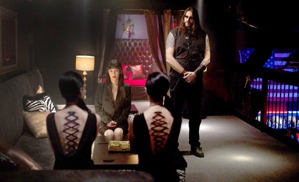 The Soska Sisters (Sylvia and Jen) ask Mary (Katherine Isabelle) for some radical body modifications in American Mary (2012) while Lance (Twan Holliday) stands guard.
