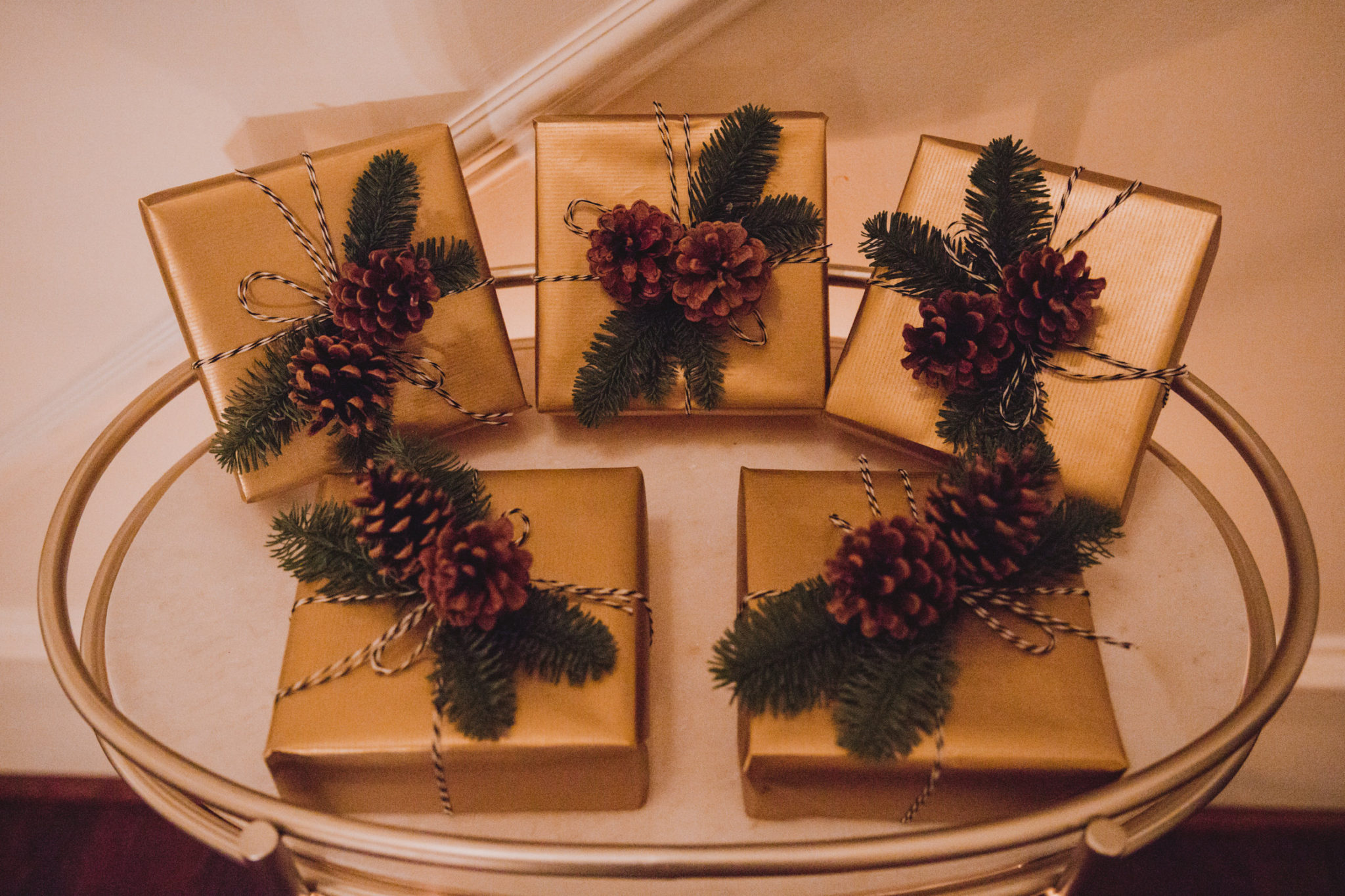 gold wrapped dinner favors with pine cones and greenery