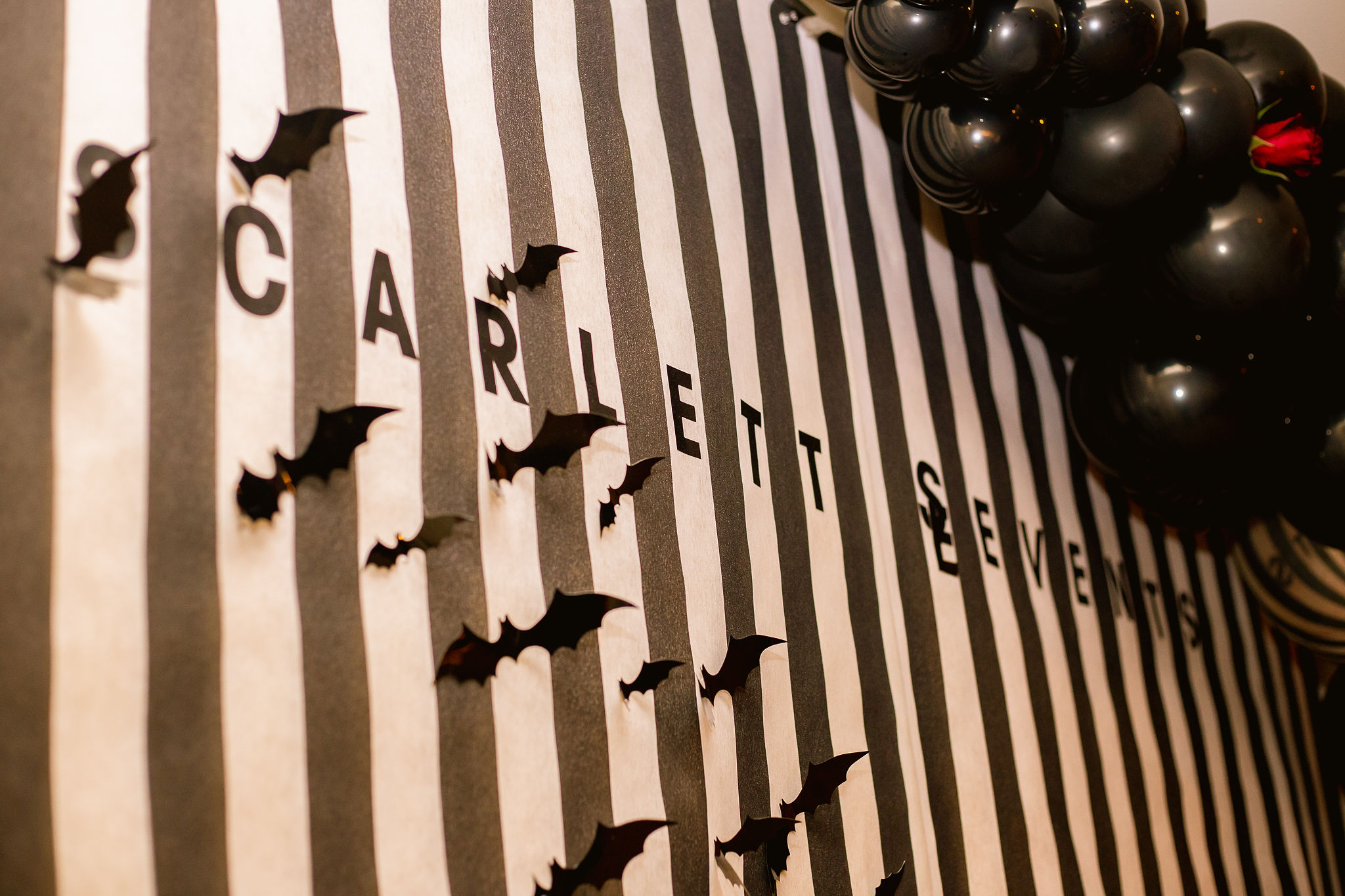 Beetlejuice inspired photo booth wall with bats and balloon installation by Scarlett Events