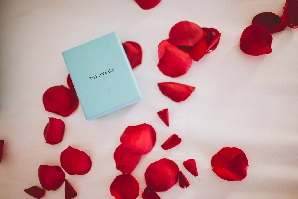 Tiffany box on bed with red rose petals