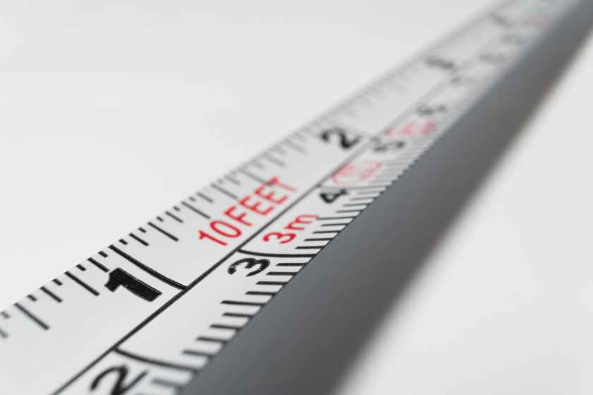 close up photo of a measuring tape on a white background, with the end fading off into the distance.
