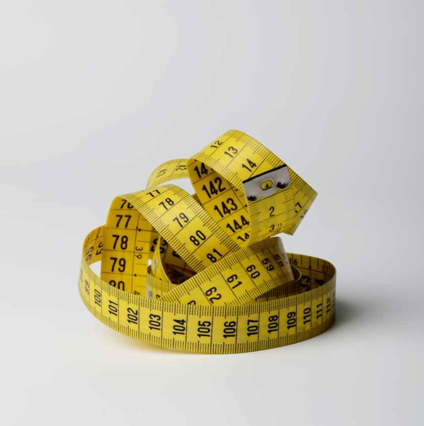 yellow measuring tape wrapped up in ball