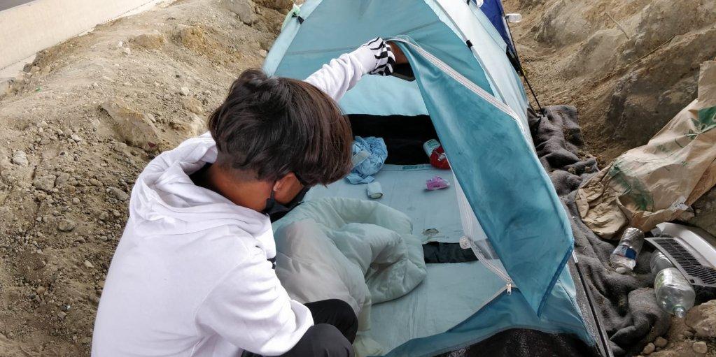 Un jeune homme montre l'intérieur de sa tente dans laquelle il dort avec un ami. Crédit : InfoMigrants