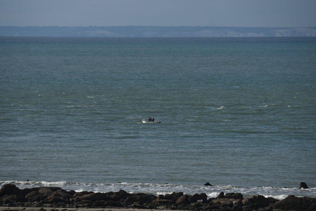 Un petit bateau navigue sur la Manche. Au loin, on distingue les falaises blanches de la côte britannique. Crédit : Mehdi Chebil pour InfoMigrants